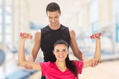Woman with her personal fitness trainer exercising with weights in gym — Stock Photo