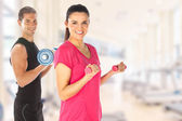 Young couple exercising with weights together in the gym — Stock Photo