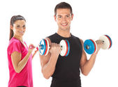 Young couple exercising with weights together — Stock Photo