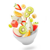 Light salad with flying fresh fruits — Stock fotografie