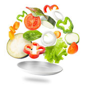 Assorted fresh vegetables flying in a plate — Stock Photo