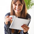 Smiling young woman with a coffee and subject a tablet — Stock Photo