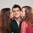 Two young women kissing handsome man standing between them — Stock Photo