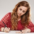 Female student writing on notebook — Stock Photo