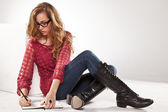 Female student writing on notebook — Stock Photo