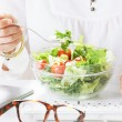 Young woman creative designer eating a salad while working in office. — Stock Photo #27267507