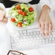 Young woman creative designer eating a salad while working in office. — Stock Photo