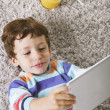 Child playing with digital tablet stretched on a carpet — Stock Photo