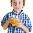 Child with plaid shirt drinking a fresh orange juice. — Stock Photo