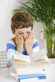 Stressed schoolboy studying in home. — Stock Photo