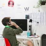 Молодой человек творческий дизайнер на телефон работает в офисе — Стоковое фото