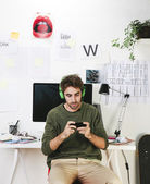 Young creative designer man at phone working at office and listening music. — Stock Photo