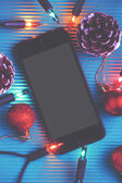 Smart phone and christmas decoration over blue background. — Stock Photo