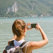 Back view of young woman taking photos with mobile phone. — Stockfoto