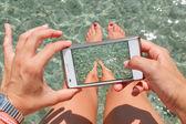 Frau fotografieren von seine füße auf dem meer. — Stockfoto