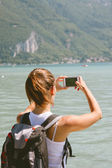 Back view of young woman taking photos with mobile phone. — Stock Photo