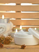 Cosmetic cream product with candles on wooden. — Stock Photo