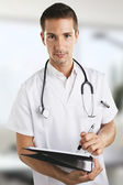 Young medical doctor man with stethoscope writting on notebook in the hospital. — Stock Photo