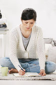Casual asian woman sitting on the floor and working in home. — ストック写真