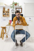 Modern creative man with smartphone on workspace. — Stock Photo