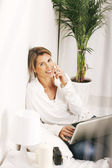 Beautiful mature business woman working with laptop in the bed. — Stock Photo