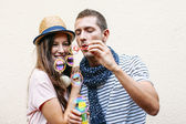 Beautiful young couple blowing soap bubbles. — Stock Photo