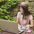 Young woman with straw hat working with laptop in outdoors. — Stock Photo #50724183