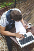 Young man working with laptop in outdoors. — Stock Photo