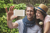 Young couple taking selfie with smart phone camera in outdoors. — Stockfoto