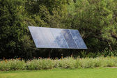 Solar panel in front of trees — Stock Photo