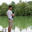 Man Fishing at a lake - Stock Photo