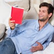 Young Brunette Man Reading A Book - Stock Photo