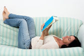 Dark haired woman lying on couch and reading a book — Stock Photo