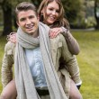 Young couple in love piggyback at a park — Stock Photo