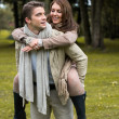 Stock Photo: Young couple in love piggyback at a park