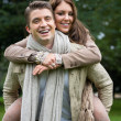 Young couple in love piggyback at a park — Stok fotoğraf