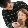 Young couple in locve eating chocolate — Stock Photo