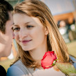 Young couple - woman with red rose — Stock Photo #18168799