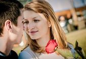 Young couple - woman with red rose — Stock Photo