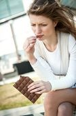 Depressed young woman eating chocolate — Stock Photo