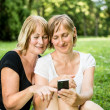 Senior mother and daughter with smartphone — Stock Photo