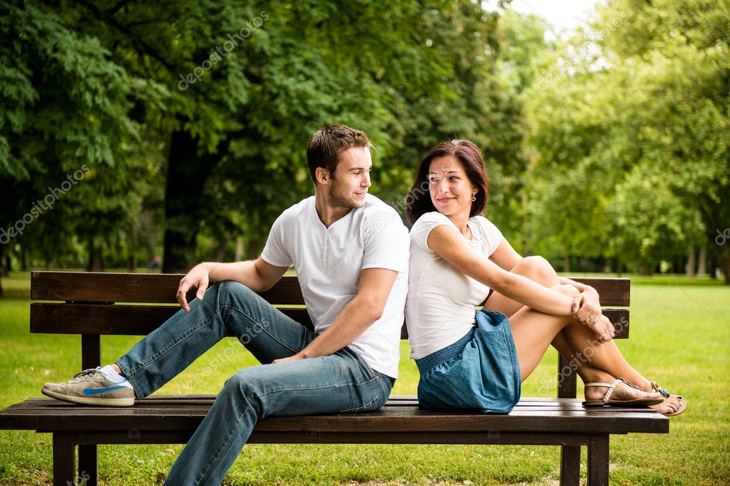 Young smiling couple looking on each other  - sitting on bench  Stock Photo #18170851