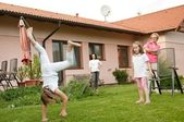 Children doing cartwheels in backyard — Stock Photo