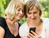 Kıdemli anne ve kızı ile smartphone — Stok fotoğraf