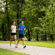 Jogging together - young couple running - Stock Photo