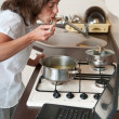 Multitasking woman - cooking meal and working — Stock Photo