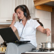 Multitasking - preparing meal and working — Stock Photo