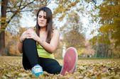Knee injury - woman sitting in pain — Stock Photo