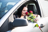 Woman with roses in car — Stock Photo
