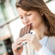 Young woman eating chocolate — Stock Photo
